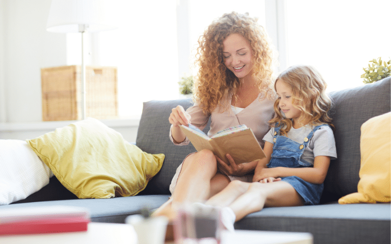 mom reading to preschooler to help them get ready to learn to read