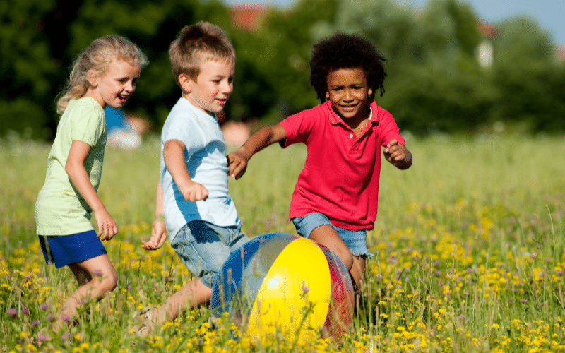 kids playing ball outside to help develop gross motor skills